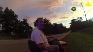 still of deputy's bodycam footage showing Paul Burke sitting on his lawnmower after having been pulled over