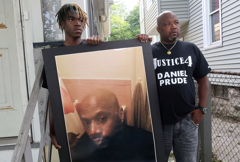 Joe Prude, right, uncle of Daniel Prude, and Daniel's nephew Armin, pictured last September in Rochester, N.Y. with a picture of Daniel Prude