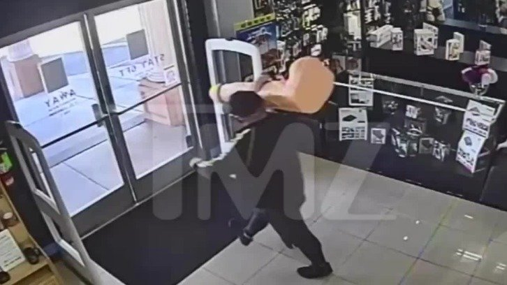 surveillance footage of the masked man heading for the store exit with the giant dildo slung over his shoulder