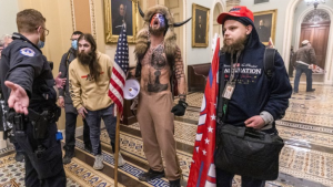 Supporters of President Donald Trump, including Jacob Chansley (center with fur hat), being confronted by Capitol Police officers outside the Senate Chamber inside the Capitol in Washington D.C.