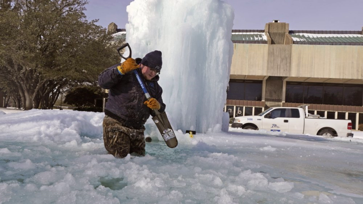A municipal worker breaking ice on a frozen fountain in Richardson, Texas, on Tuesday, Feb. 16, 2021