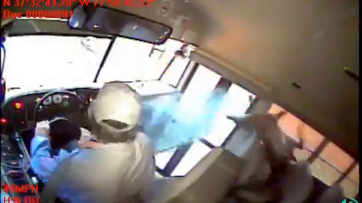 still of bus footage showing deer landing on a sleeping student in the first row