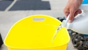 bleach being poured into yellow bucket