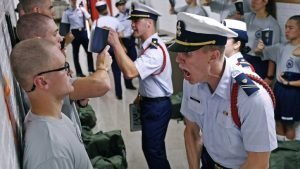 Whisky 2 company Cadre Jacob Denns, right, shouts instructions to swab Nicolas Fisher, left, of Pelham, N.H., on the first day of last summer's seven-week indoctrination to military academy life for the Class of 2023 at the U.S. Coast Guard Academy in New London, Conn.