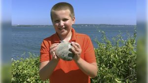 Cooper Monaco holding the large quahog he found Monday while clamming with his grandfather in Westerly, Rhode Island