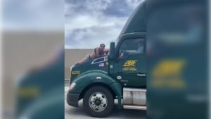 Screengrab of video showing the unidentified man clinging to the hood of a moving semi-trailer on a Florida highway