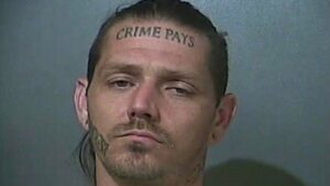 """Police mugshot of Donald Murray of Terre Haute, Indiana, who has the words """"CRIME PAYS"""" tattooed on his forehead"""