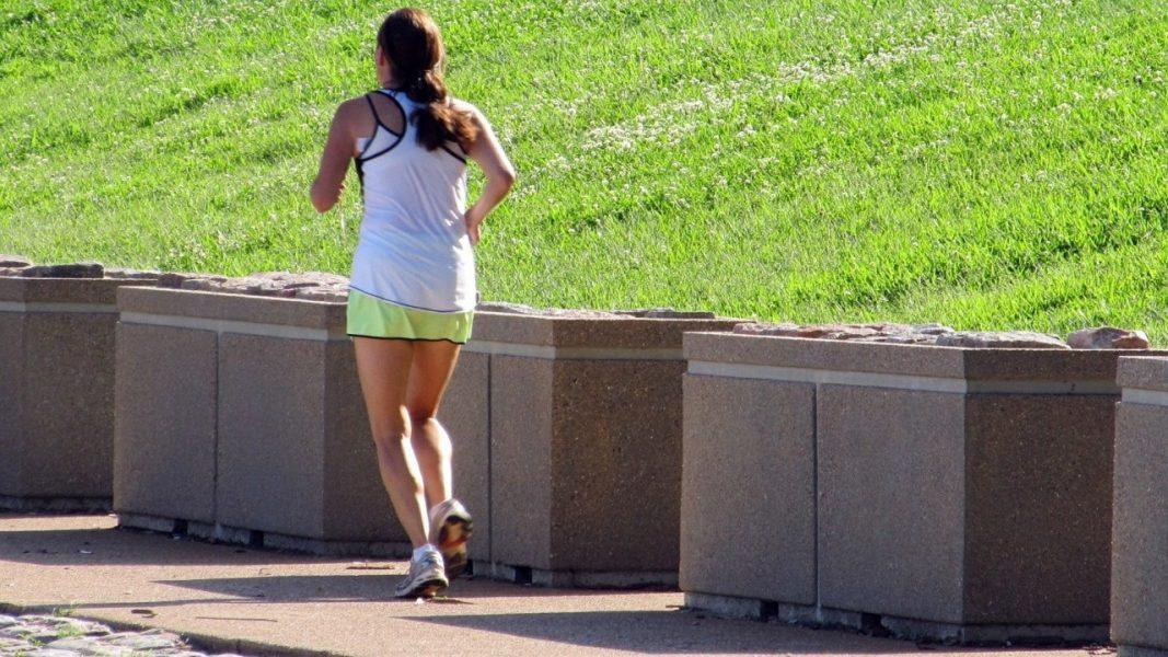 woman jogging near grass bank