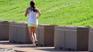 woman jogging near grass bank