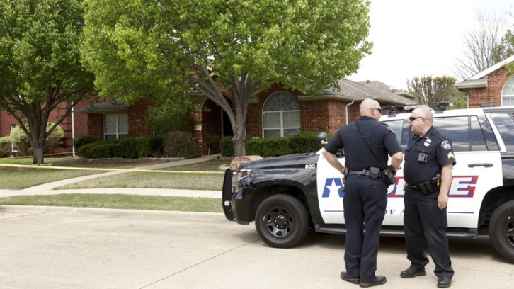 Police officers stand outside a suburban Dallas home, where six people were found fatally shot after two brothers allegedly planned to kill four family members and themselves